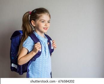 portrait of a smiling schoolgirl in uniform with school backpack
