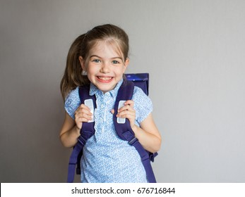 portrait of a smiling schoolgirl in uniform with school backpack
