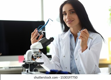 Portrait of smiling scientist using microscope and writing important result. Beautiful lady wearing medical white coat. Medicine and research concept. Blurred background