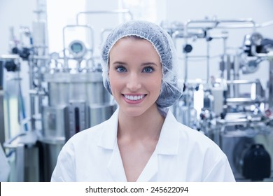 Portrait of a smiling scientist wearing hair net in the factory