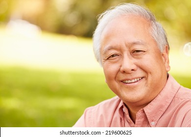 Portrait Of Smiling Senior Asian Man Sitting In Park