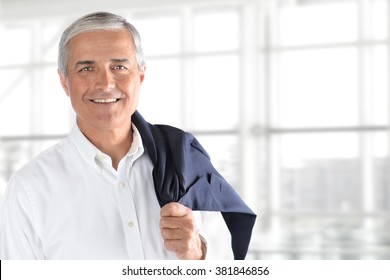 Portrait of smiling senior businessman standing against office window background while looking at camera, with his coat over his shoulder