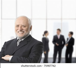 Portrait of smiling senior businessman standing with arms folded, businesspeople in background.?