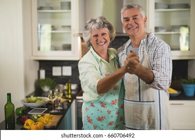 Portrait of smiling senior couple dancing in kitchen at home