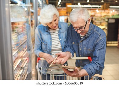 Portrait of smiling senior couple grocery shopping in supermarket, reading shopping list leaning on cart standing by freezers