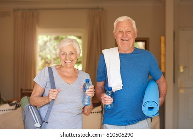 Portrait of a smiling senior couple in sportswear carrying yoga mats and water standing together in their living room at home