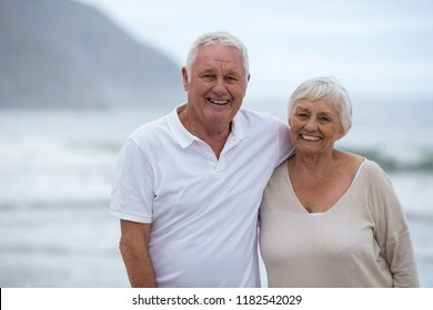 Portrait of smiling senior couple standing together at beach