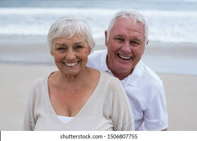 Portrait of smiling senior couple standing on the beach