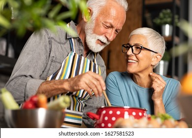 Portrait of smiling senior couple standing close together, cuddling caringly and laughing, cooking at kitchen table