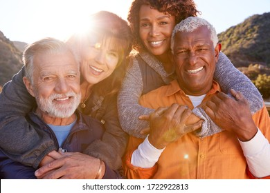 Portrait Of Smiling Senior Friends Having Fun Walking In Countryside Together