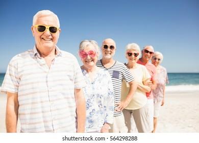 Portrait of smiling senior friends on the beach