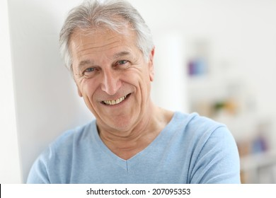 Portrait of smiling senior man with blue shirt