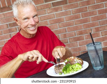 Portrait of smiling senior man eating strip steak served with loaded baked potato and broccoli at restaurant table