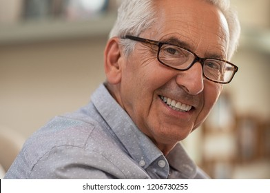 Portrait of smiling senior man with eyeglasses looking at camera. Successful mature man wearing spectacles at home. Closeup face of handsome elder with glasses and toothy smile.