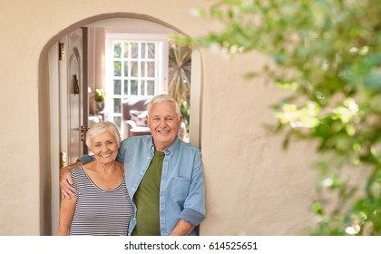 Portrait of a smiling senior man with his arm around his wife's shoulder while standing together at the front door of their home