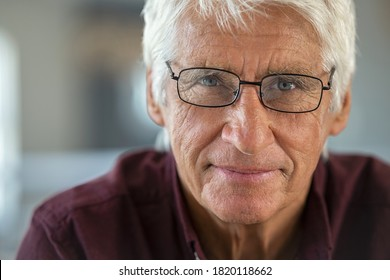 Portrait of smiling senior man looking at camera. Handsome old man with white hair wearing eyeglasses with satisfaction. Close up face of proud and satisfied mature male sitting on couch.