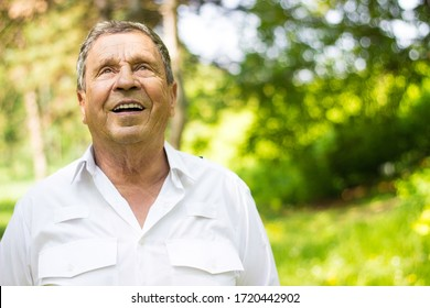 Portrait of a smiling senior man in Nature, looking away