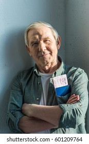 portrait of smiling senior man with passports and tickets in pocket, traveling concept