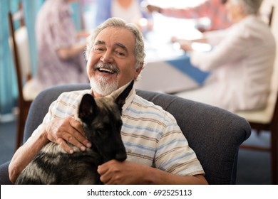 Portrait of smiling senior man sitting with puppy on chair at retirement home