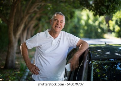 Portrait of smiling senior man standing by car