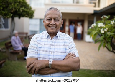 Portrait of smiling senior man standing with arms crossed against retirement home