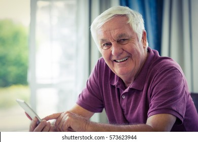 Portrait of smiling senior man using mobile phone at home