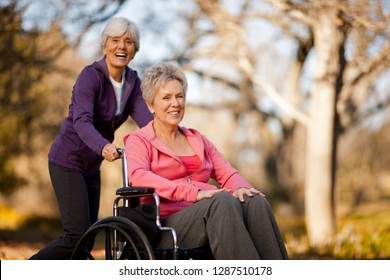 Portrait of a smiling senior woman being pushed through a park in a wheelchair by her friend.
