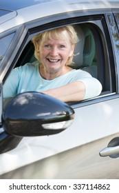 Portrait Of Smiling Senior Woman Driving Car