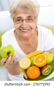 Portrait of a smiling senior woman holding a variety of fruits in her hands