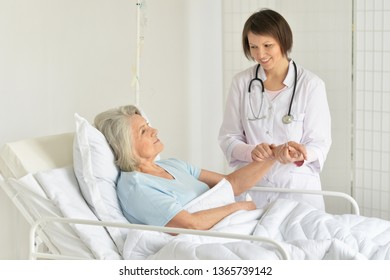 Portrait of smiling senior woman in hospital with caring doctor
