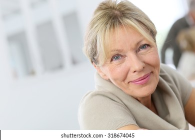 Portrait of smiling senior woman, people in background