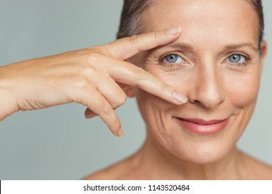 Portrait of smiling senior woman with perfect skin showing victory sign near eye on grey background.  Closeup face of mature woman showing successful results after anti-aging wrinkle treatment.