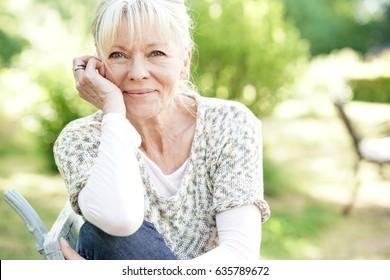 Portrait of smiling senior woman relaxing in garden
