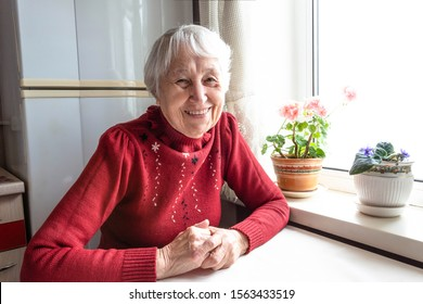 Portrait of smiling senior woman, sitting at home and looking at camera.