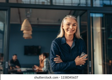 Portrait of smiling senior woman standing in office doorway with her arms crossed. Beautiful female executive at office with people meeting in background.