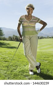 Portrait of a smiling senior woman standing on golf course