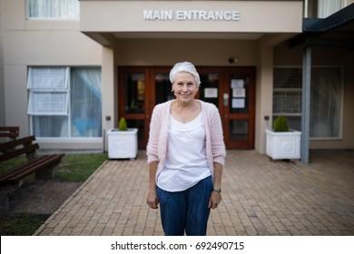 Portrait of smiling senior woman standing against house entrance
