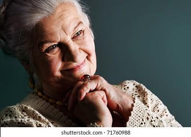 Portrait of a smiling senior woman. Studio shot over grey background.