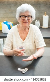 Portrait of smiling senior woman taking pills at home.