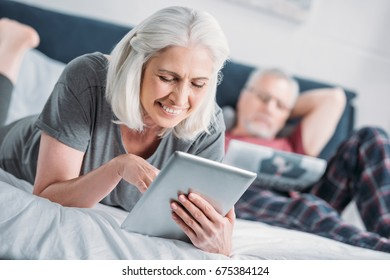 portrait of smiling senior woman using tablet while resting on bed