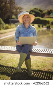 Portrait of smiling senior woman using laptop in park on a sunny day