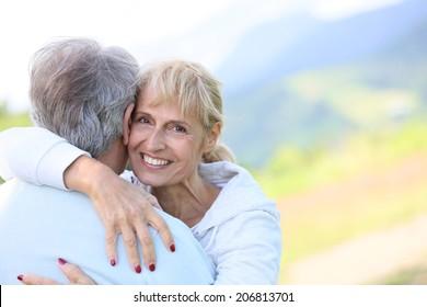 Portrait of smiling senoir woman embracing her husband