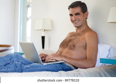 Portrait of smiling shirtless middle aged man working on laptop