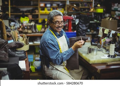 Portrait of smiling shoemaker applying glue on shoe in workshop