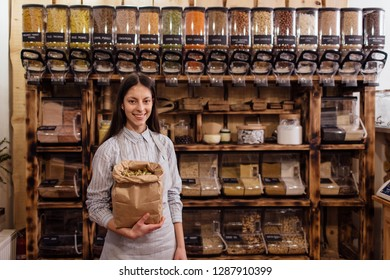Portrait of smiling shopkeeper in package free grocery store with food containers in background. Cheerful shop assistant holding paper bag full of dried herb leaves in zero waste shop.
