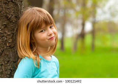 Portrait of smiling shy girl posing in the nature on beautiful spring day.