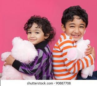 Portrait of Smiling Siblings Clutching Their Stuffed Toys