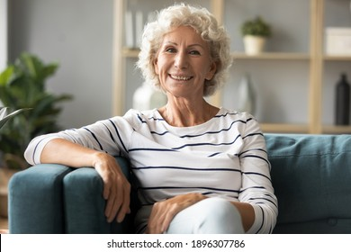 Portrait of smiling sincere mature retired grey-haired woman relaxing on comfortable sofa in living room. Happy beautiful older caucasian grandmother enjoying peaceful leisure time, looking at camera.