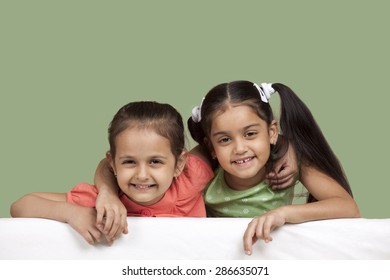 Portrait of smiling sisters over colored background