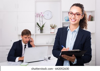 portrait of smiling spanish business woman holding cardboard in office